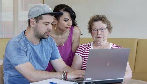 Twee Stip vrijwilligers in midden helpen een oudere mevrouw achter de laptop